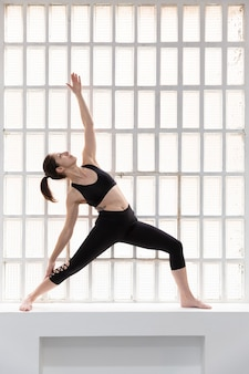 Młoda dziewczyna kaukaski w czarnej odzieży sportowej robi ćwiczenia jogi obok dużego okna w jej studio. miejsce na tekst.