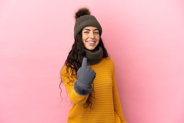 Młoda dziewczyna kaukaski z czapka zimowa na białym tle na fioletowym tle robi nadchodzący gest