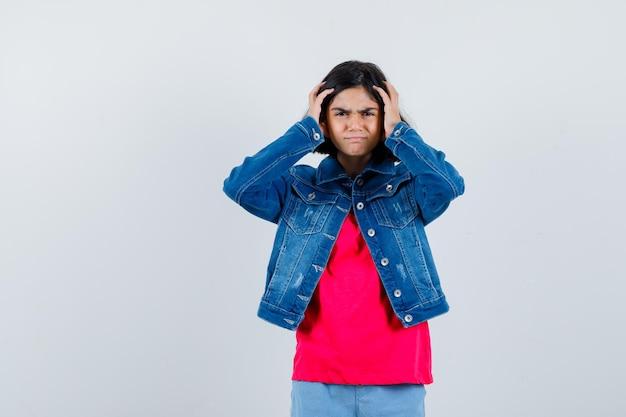 Młoda dziewczyna, kładąc ręce na głowie w czerwonej koszulce i dżinsowej kurtce i patrząc nękany, widok z przodu.