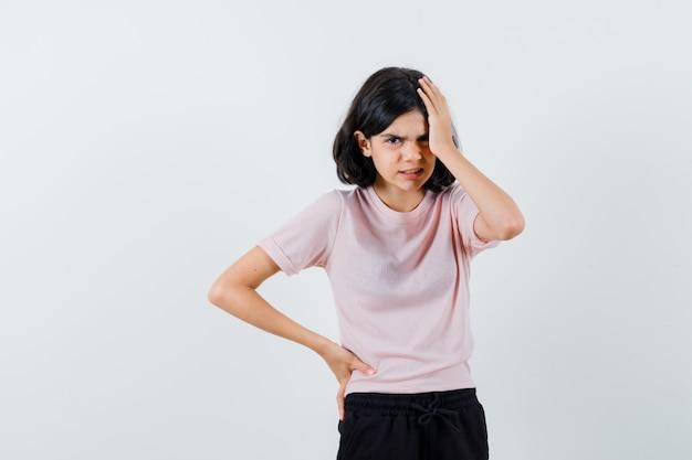 Młoda dziewczyna kładąc rękę na głowie trzymając rękę na talii w różowej koszulce i czarnych spodniach i patrząc zły