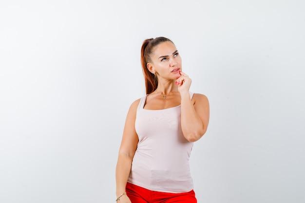 Młoda dziewczyna kładzie rękę na brodzie, myśląc o czymś w beżowym topie i czerwonych spodniach