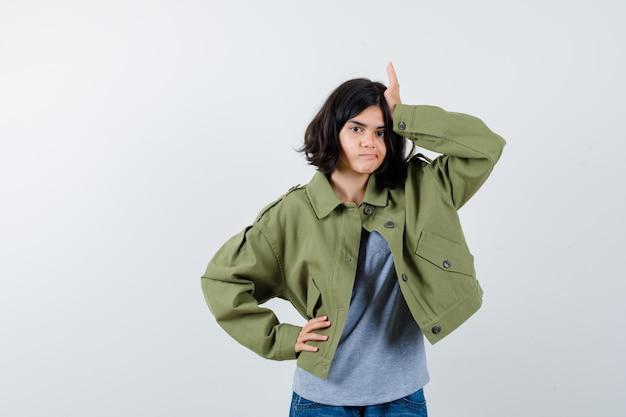 Młoda dziewczyna kładzie rękę na głowie, trzymając rękę na pasie w szary sweter, kurtka khaki, spodnie jeansowe i wyglądający ładny, widok z przodu.
