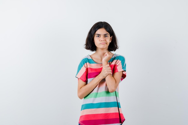 Młoda dziewczyna kładzie rękę na przedramieniu w kolorowe paski t-shirt i wygląda poważnie. przedni widok.