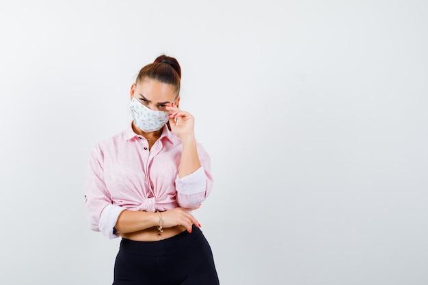 Młoda dziewczyna kładzie rękę na skroni, trzymając jedną rękę pod łokciem w różowej bluzce, czarnych spodniach, masce i wyglądającej na złą. przedni widok.