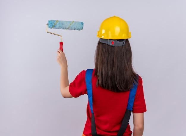 Młoda dziewczyna konstruktora stoi tyłem do aparatu i trzyma wałek do malowania na na białym tle
