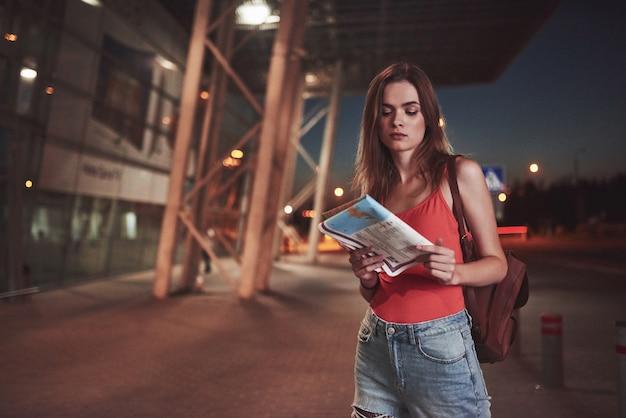 Młoda dziewczyna kosztuje w nocy w pobliżu terminala lotniska lub dworca i czytając mapę miasta