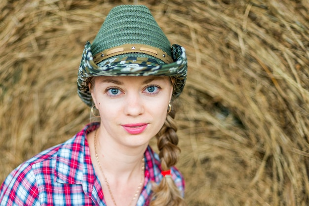 Młoda dziewczyna kraju w czerwonej koszuli w kratę i kowbojski kapelusz uśmiecha się