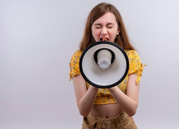 Młoda dziewczyna krzyczy w głośniku na na białym tle białej ścianie z miejsca na kopię