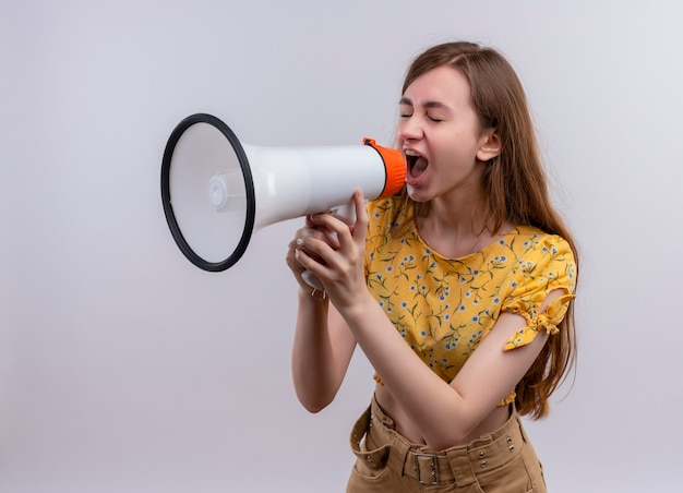 Młoda dziewczyna krzyczy w głośniku po lewej stronie na na białym tle białej ścianie