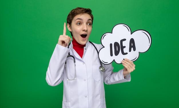 Młoda dziewczyna lekarz w białym fartuchu ze stetoskopem, trzymając znak dymek z pomysłem na słowo, wyglądający na szczęśliwy i zaskoczony pokazując palec wskazujący stojący na zielono