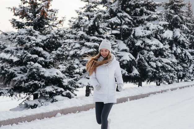Młoda dziewczyna lekkoatletycznego biegnie w parku w słoneczny zimowy dzień. zdrowy styl życia.
