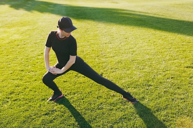 Młoda dziewczyna lekkoatletycznego w czarnym mundurze, czapka robi ćwiczenia sportowe, rozgrzewka, rozciąganie przed uruchomieniem na zielony trawnik w parku na zewnątrz w słoneczny letni dzień. fitness, koncepcja zdrowego stylu życia.