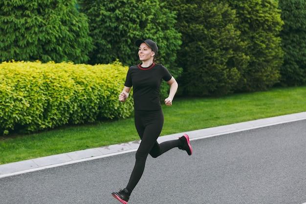 Młoda dziewczyna lekkoatletycznego w czarnym mundurze i treningu czapki, robienie ćwiczeń sportowych, bieganie, patrząc prosto na ścieżkę w parku miejskim na zewnątrz na wiosenny lub letni słoneczny dzień. fitness, koncepcja zdrowego stylu życia.