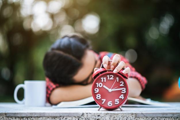 Młoda dziewczyna leżąc na biurku po przeczytaniu książki