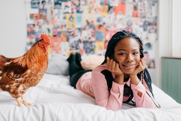 Młoda dziewczyna leżąc na łóżku z kurczakiem