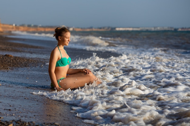 Młoda dziewczyna leżąc na plaży w surf w morzu w strój kąpielowy