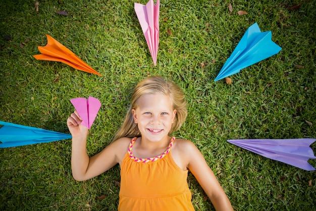 Młoda dziewczyna leżąc na trawie wokół papierowych samolotów