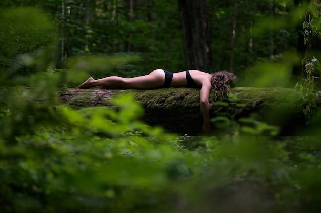 Młoda dziewczyna leży na powalonym drzewie w lesie