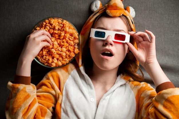 Młoda dziewczyna leży na szarym tle w okularach 3d, je popcorn i ogląda film