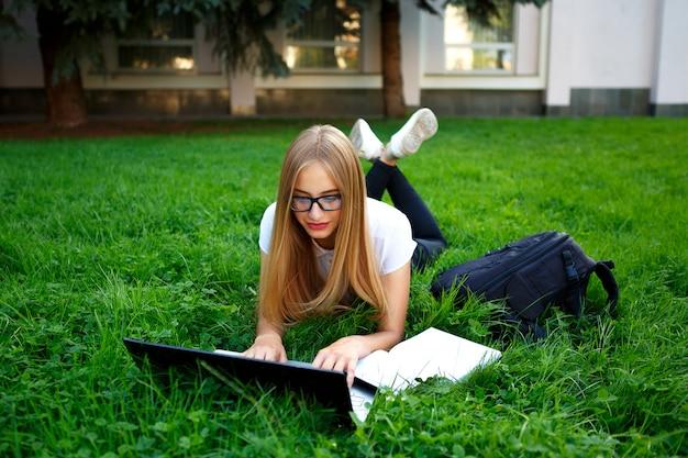 Młoda dziewczyna leży na trawie w parku, studiuje z laptopem