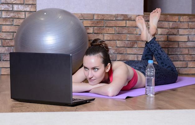 Młoda dziewczyna leży z rękami pod głową na macie do jogi i patrzy na ekran laptopa. fitness w domu