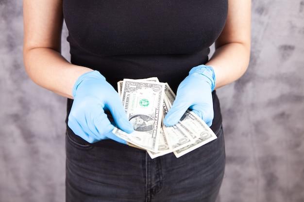 Młoda dziewczyna liczy pieniądze w rękawiczkach