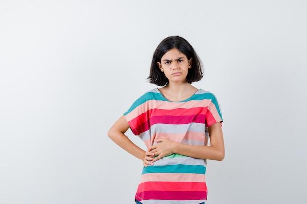 Młoda dziewczyna ma ból brzucha, krzywiąc się w kolorowe paski t-shirt i wyglądając na zmęczoną, widok z przodu.