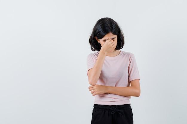 Młoda dziewczyna ma ból głowy w różowej koszulce i czarnych spodniach i wygląda na wyczerpaną