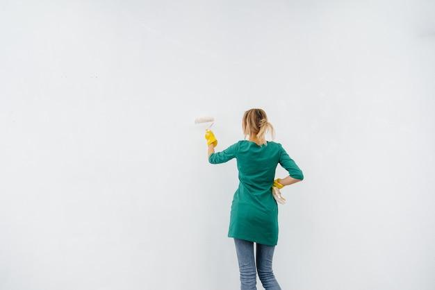 Młoda dziewczyna maluje wałkiem białą ścianę. naprawa wnętrza.