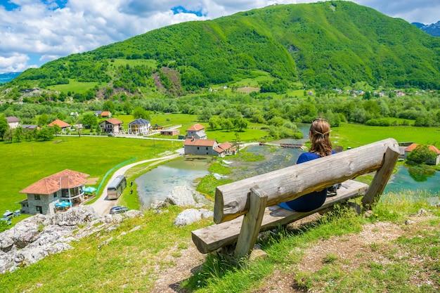 Młoda dziewczyna marzy na drewnianej ławce w pobliżu źródeł ali paszy.