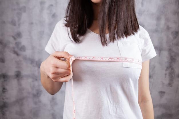 Młoda dziewczyna mierzy obwód piersi na szaro