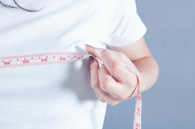 Młoda dziewczyna mierzy piersi