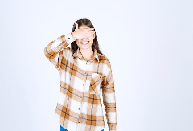 Młoda dziewczyna model stojący i zasłaniając oczy ręką na biało szarej ścianie.