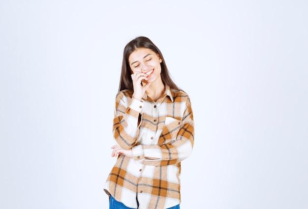 Młoda dziewczyna model stojący na biało szarej ścianie.