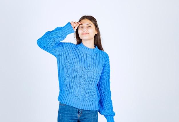 Młoda dziewczyna model w niebieskim swetrze, trzymając rękę w pobliżu czoła.