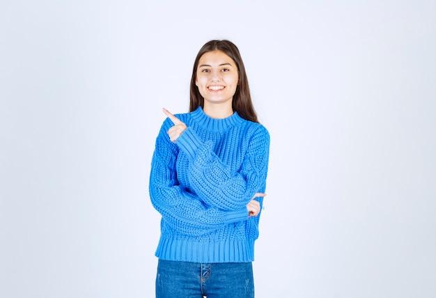 Młoda dziewczyna model w niebieskim swetrze, wskazując na biało-szary.