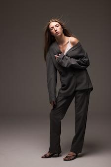 Młoda dziewczyna model w popielatym mężczyzna kostiumu pozyci w studiu