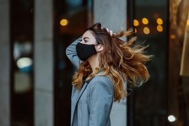 Młoda dziewczyna, modelka, z profilu, poruszająca włosami, w amerykańskiej marynarce i masce na twarz.