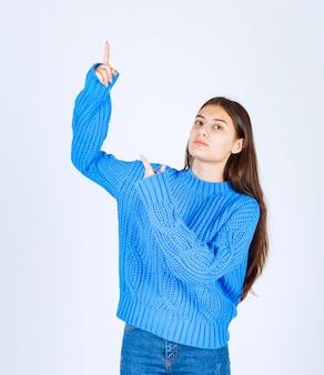 Młoda dziewczyna modelu wskazując na białej ścianie.