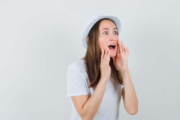 Młoda dziewczyna mówi sekret w białej czapce i wygląda na zdumioną