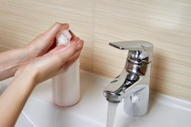 Młoda dziewczyna myje ręce mydłem i wodą. zapobieganie chorobom wirusowym. zbliżenie, selektywne focus