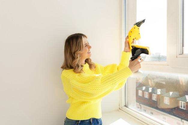 Młoda dziewczyna myje szyby przy użyciu urządzenia do mycia okien. koncepcja sprzątania domu i czystych okularów.