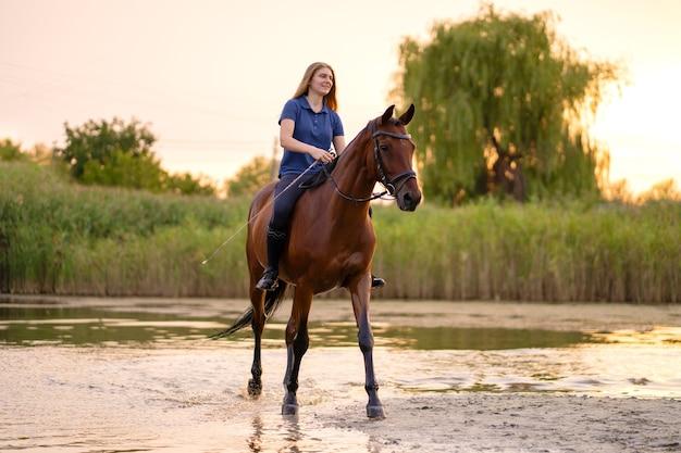 Młoda dziewczyna na koniu po płytkim jeziorze. koń biegnie po wodzie o zachodzie słońca