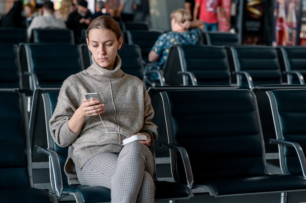 Młoda dziewczyna na lotnisku czeka na jej odlot. przewijany smartfon
