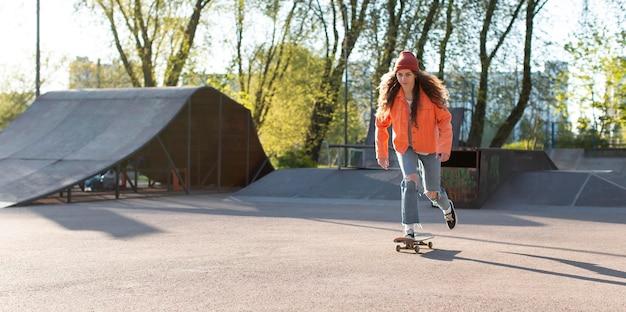 Młoda dziewczyna na łyżwach na zewnątrz pełny strzał