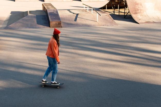 Młoda dziewczyna na łyżwach w parku pełnym strzału