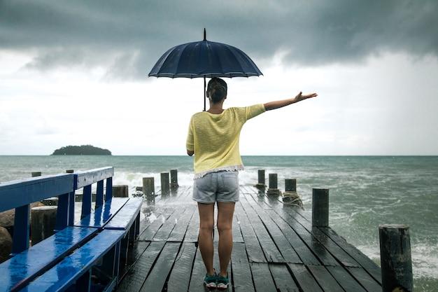 Młoda dziewczyna na molo z parasolem stoi plecami do morza