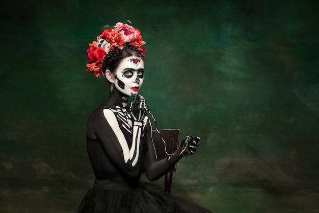 Młoda dziewczyna na obrazie santa muerte, świętej śmierci lub cukrowej czaszki