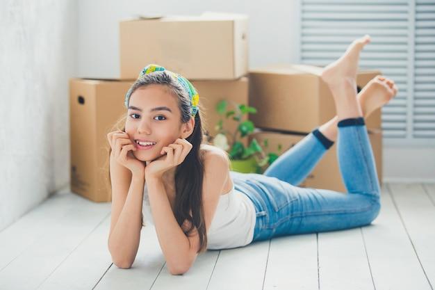 Młoda dziewczyna na podłodze z pudełkami do przenoszenia
