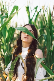 Młoda dziewczyna na polu kukurydzy. trend - twarz dziewczyny z liśćmi kukurydzy. jedność z naturą. w trosce o środowisko